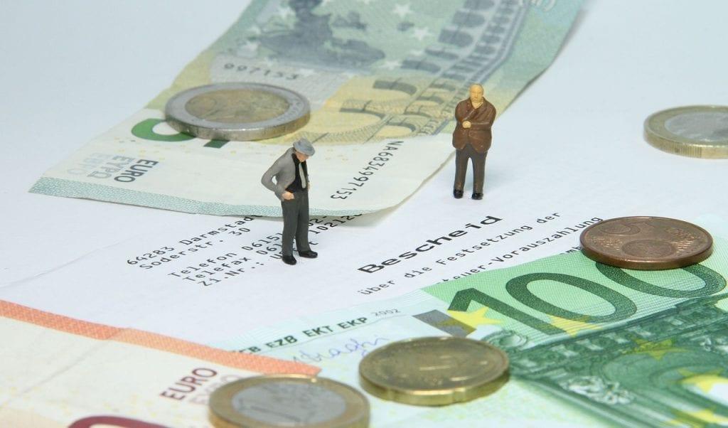Ein Bescheid über die Festsetzung der Grundsteuer-Vorauszahlung mit Euro-Scheinen und Münzen sowie zwei kleinen Figuren